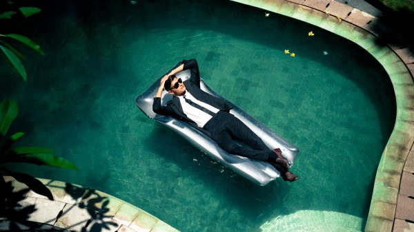 business man relaxing in the pool wearing a suit