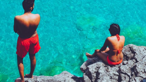 man and woman sitting on cliffs in bathing suits