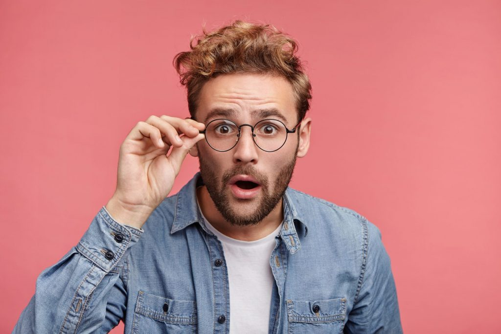 suprised man wearing glasses on pink background