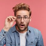 suprised man wearing glasses on pink background