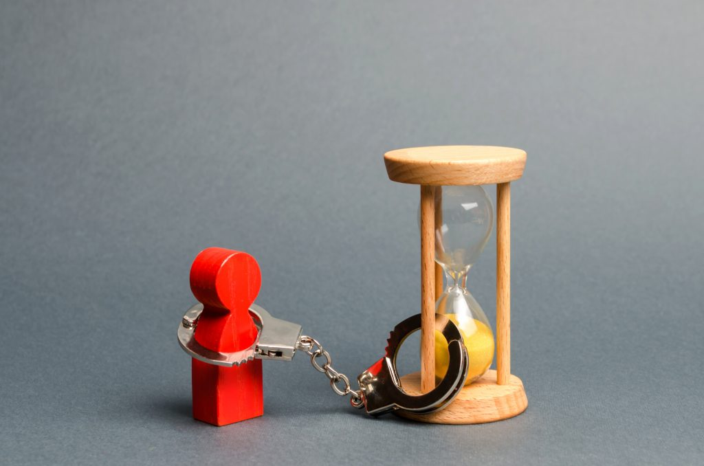 red figure hancuffed to an hourglass