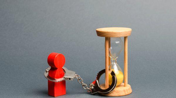 red figure hancuffed to an hourglass